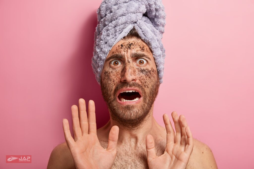 batchfrightened handsome young caucasian man with coffee scrub face makes stop gesture afraids spa treatments wears towel